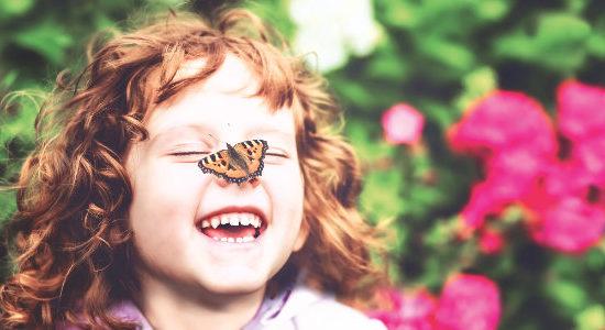 Lachendes Mädchen mit Schmetterling auf der Nase. Im Hintergrund Blumen.